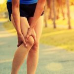 woman holds knee on running path